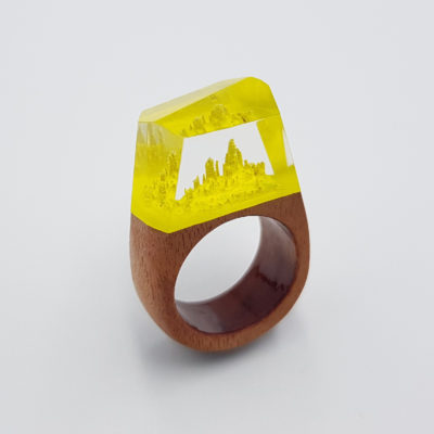 Resin ring in yellow color with wooden base